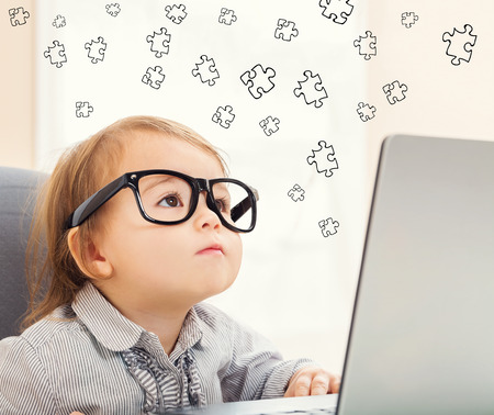 mixed race children: Puzzle concept with toddler girl using her laptop Stock Photo