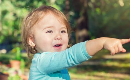 밝은 여름날에 밖에 서 놀고있는 행복한 유아 소녀