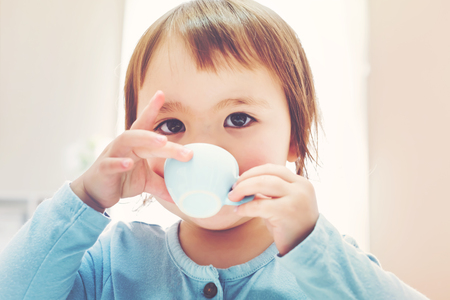teacup: Happy toddler girl drinking from a tiny teacup