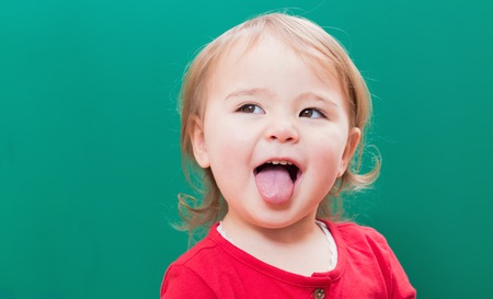 out: Happy toddler girl sticking her tongue out in front of a green chalkboard