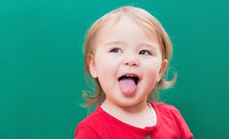 adentro y afuera: Muchacha feliz del ni�o que se pega la lengua hacia fuera delante de una pizarra verde