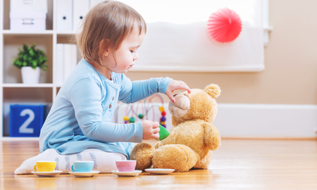 babies playing: Happy toddler girl have tea with her teddy bear