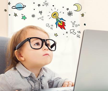 그녀의 노트북을 사용하는 유아 소녀와 아이디어 로켓 개념