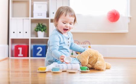 Het gelukkige peutermeisje heeft thee met haar teddybeer