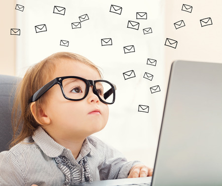 contact: Email concept with toddler girl using her laptop