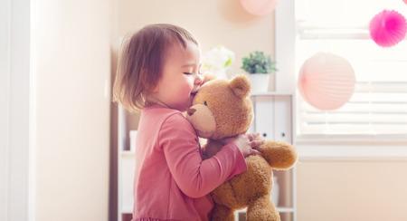 Glückliches Kleinkindmädchen mit ihrem Teddybären im Haus spielen Standard-Bild - 54662532