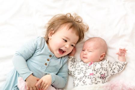 Glückliches Kleinkindmädchen mit ihrem neugeborenen Schwester spielen Standard-Bild - 54581182