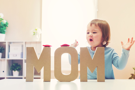 Toddler girl celebrating Mothers Day with big MOM letters