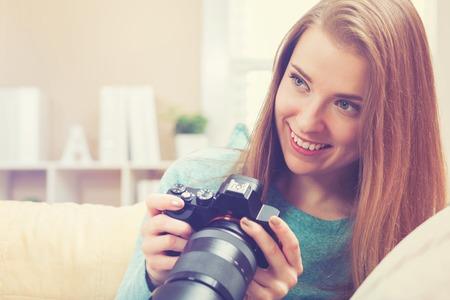 dslr: Young female photographer using a DSLR camera