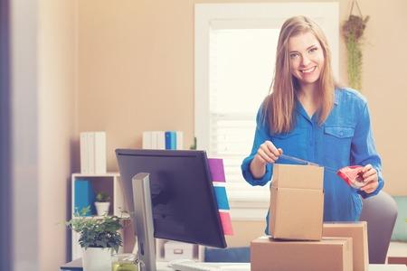 Mujer joven grabación cajas para ser enviado en su oficina en casa Foto de archivo