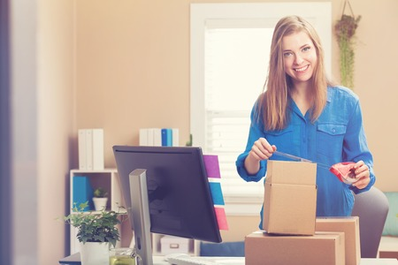 Young woman taping boxes to be shipped in her home office Stock Photo