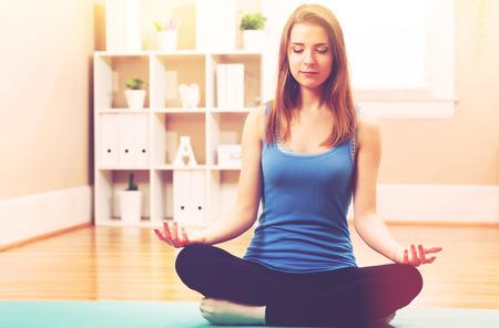 joven la práctica de la meditación en casa Foto de archivo