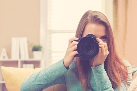 camera girl: Young female photographer using a DSLR camera