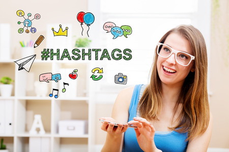 woman smartphone: Hashtags concept with young woman wearing white glasses using her smartphone in her home