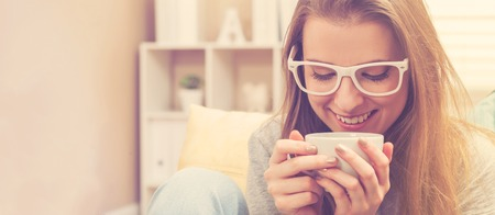 woman couch: Happy young woman drinking coffee on her couch at home