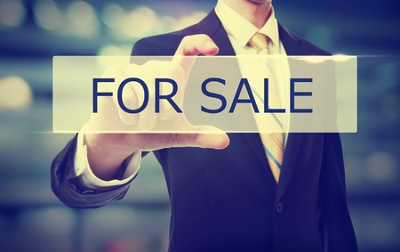 finacial: Business man holding For Sale on blurred abstract background