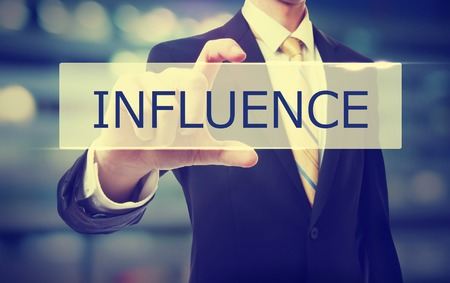 influence: Business man holding Influence on blurred abstract background Stock Photo