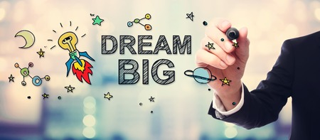 Businessman drawing Dream Big concept on blurred abstract background Stock Photo
