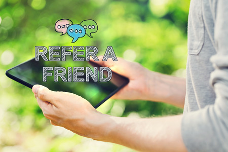 Refer A Friend concept with young man holding his tablet computer outside in the park Stock Photo