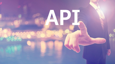 api: API concept with businessman on blurred city background