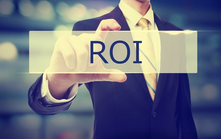Business man holding ROI on blurred abstract background