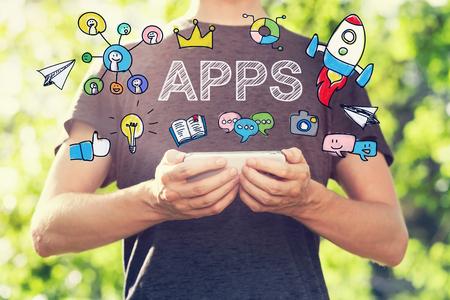 Koncepcja Aplikacje z młody mężczyzna trzymając smartfon na zewnątrz w parku w stronę słońca