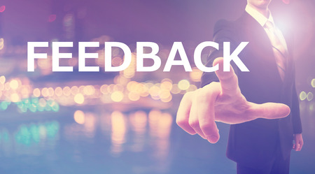 Feedback concept with businessman on blurred city background Stock Photo