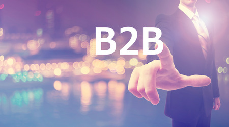 b2b: B2B concept with businessman on blurred city background