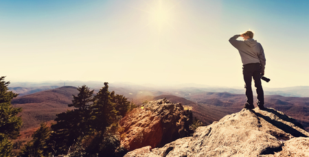 edge of cliff: Man with a camera standing on at the edge of a cliff overlooking the mountains