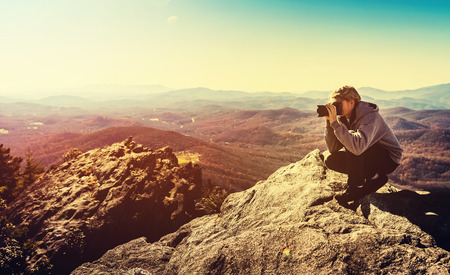edge of cliff: Man with a camera at the edge of a cliff overlooking the mountains below