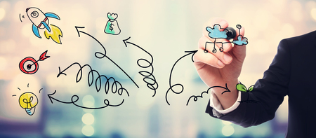business opportunity: Businessman drawing arrows and cartoon on blurred abstract background