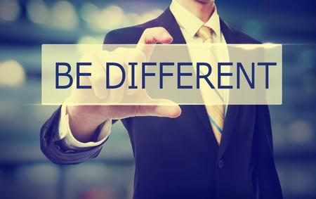 Holding dell'uomo di affari Be Different su sfondo sfocato astratto