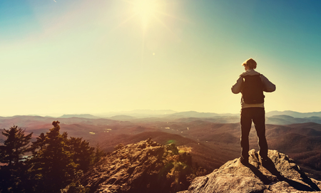 edge of cliff: Man standing at the edge of a cliff overlooking the mountains below