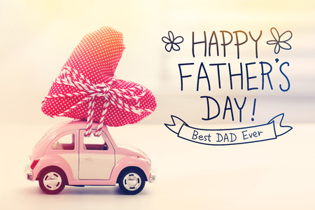 Happy Fathers Day message with a miniature pink car carrying a heart cushion