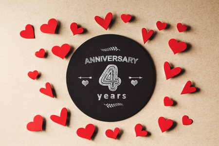 aniversario de boda: Aniversario 4 años mensaje con pequeños corazones de papel hechas a mano Foto de archivo