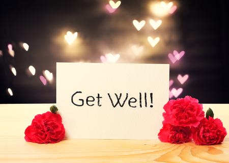 well: Get Well message card with carnation flowers and heart shaped lights Stock Photo