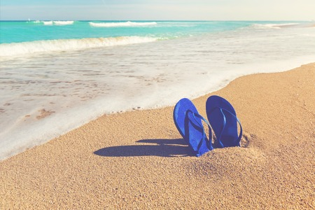 Blue sandals stuck in the sand of a tropical beach Stock Photo