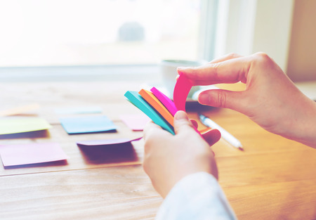organizing: Person organizing things with pastel sticky notes at a desk