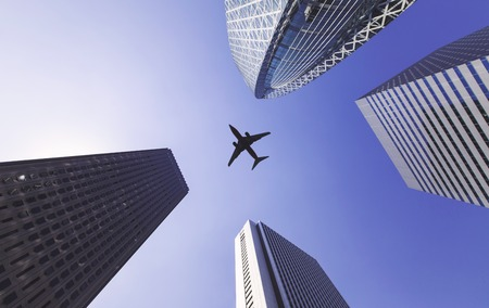 appears: Airplane appears between tall city buildings Stock Photo