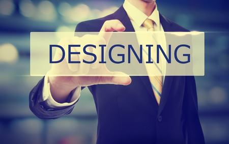 designing: Business man holding Designing on blurred abstract background