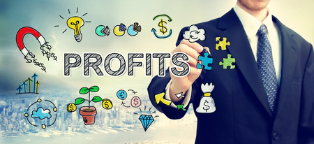 profits: Businessman drawing Profits concept above the city Stock Photo