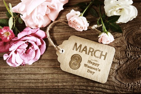womans: Womans Day message with rustic pink roses on wooden table