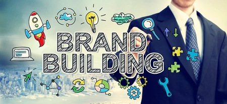 Businessman drawing Brand Building concept above the city