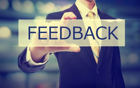 Business man holding Feedback on blurred abstract background Stock Photo