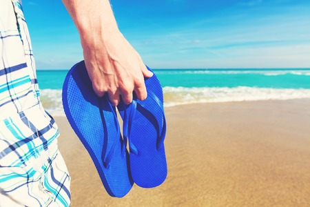Man holding his sandals at on a tropical beach Stock Photo