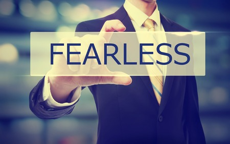 fearless: Business man holding Fearless on blurred abstract background