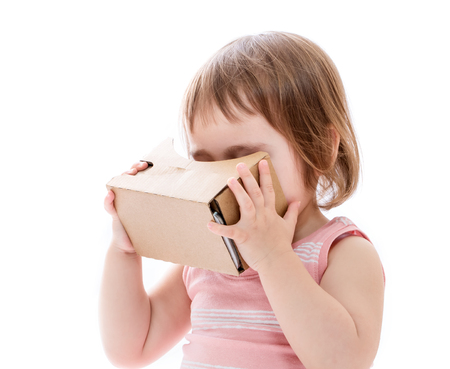 ar: Toddler girl using a new virtual reality headset isolated on white background Stock Photo
