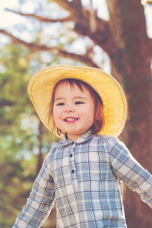 babies playing: Happy toddler girl in a hat playing outside Stock Photo