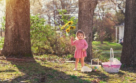 asian lifestyle: Happy toddler girl playing outside with an Easter basket