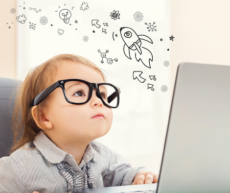 mixed race children: Rocket and Gears concept with toddler girl using her laptop Stock Photo